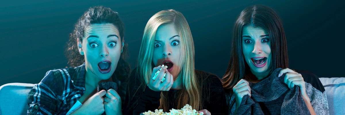 Three women watching a scary movie eating popcorn. List of Halloween movies on netflix