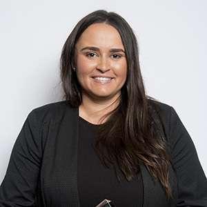 Lizzy Clarkson, Macquarie Uni STEM Ambassador stands against a white wall wearing a black blazer